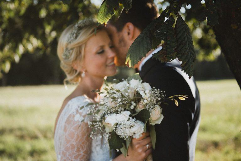 Hochzeitsfotografie Hamburg-Frau-Siemers-Gut Basthorst- Portrait Brautpaar unter Kastanienbaum-Schaut verliebt in die Ferne.
