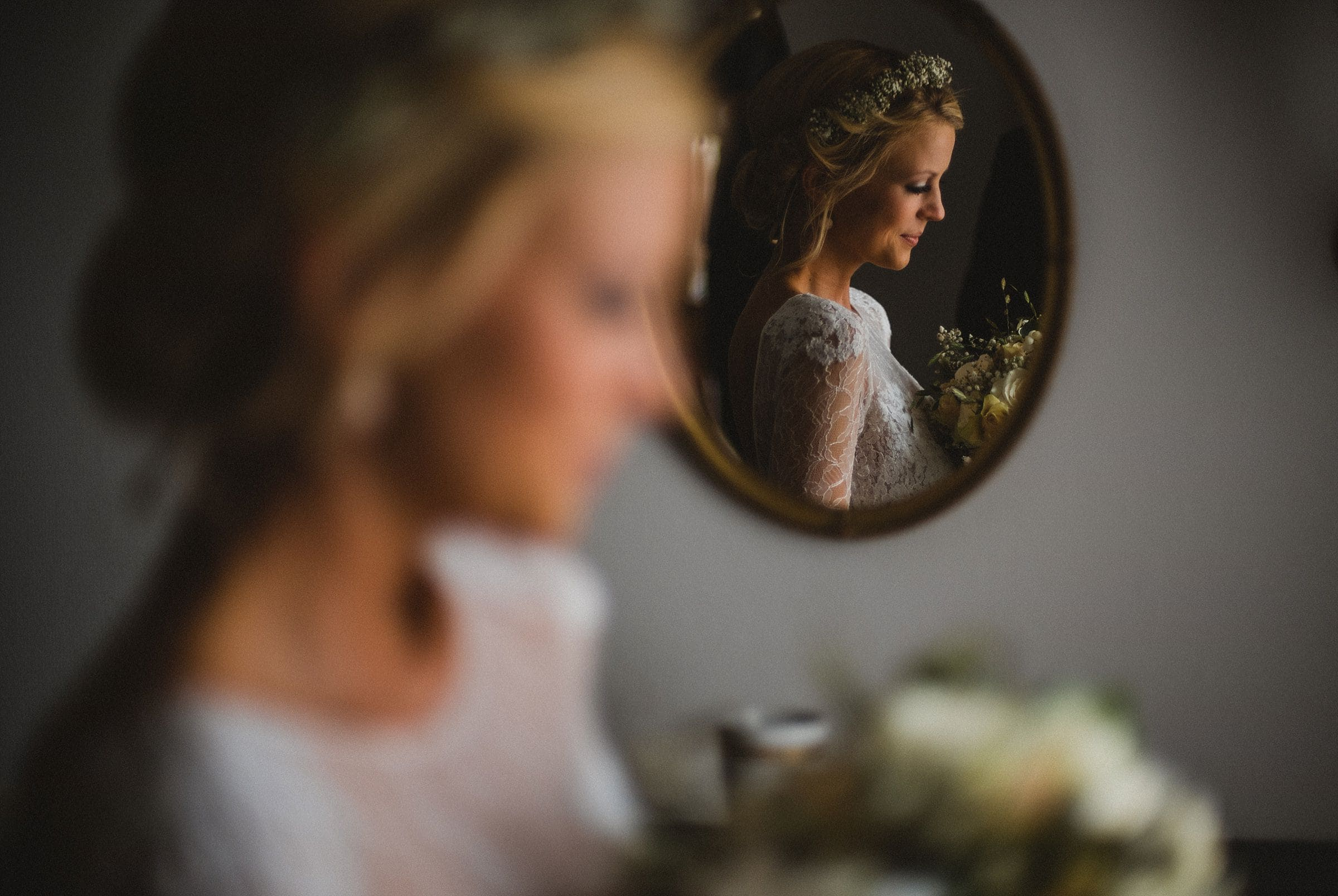 Hochzeitsfotografie Hamburg-Frau-Siemers-Gut Basthorst- Braut schaut auf den Brautstrauß, spiegelt sich im Spiegel