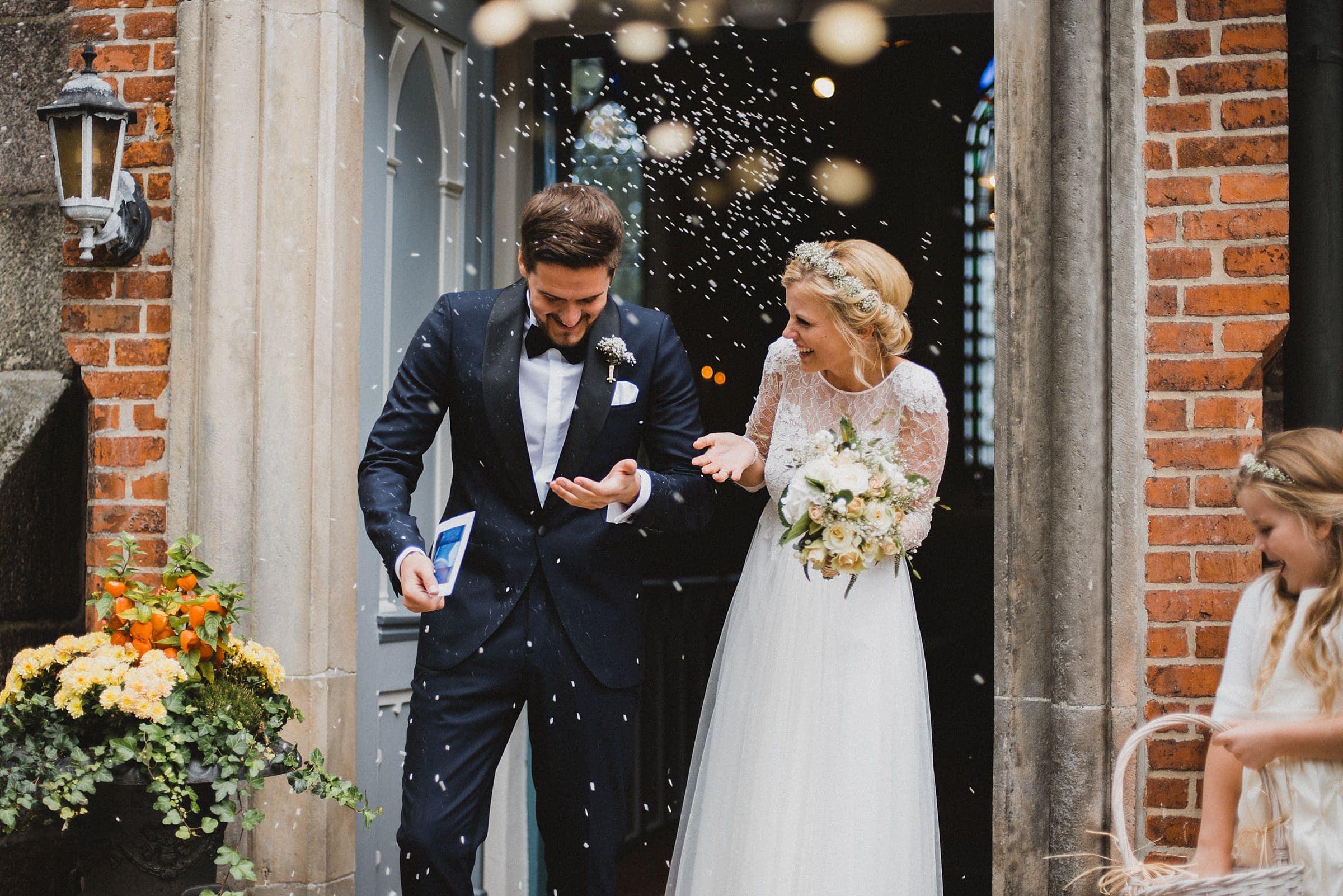 Hochzeitsfotografie Hamburg-Frau-Siemers-Gut Basthorst- Frisch verheiratet marschiert das Brautpaar aus der Kirche. Alle Gäste werfen mit Reis