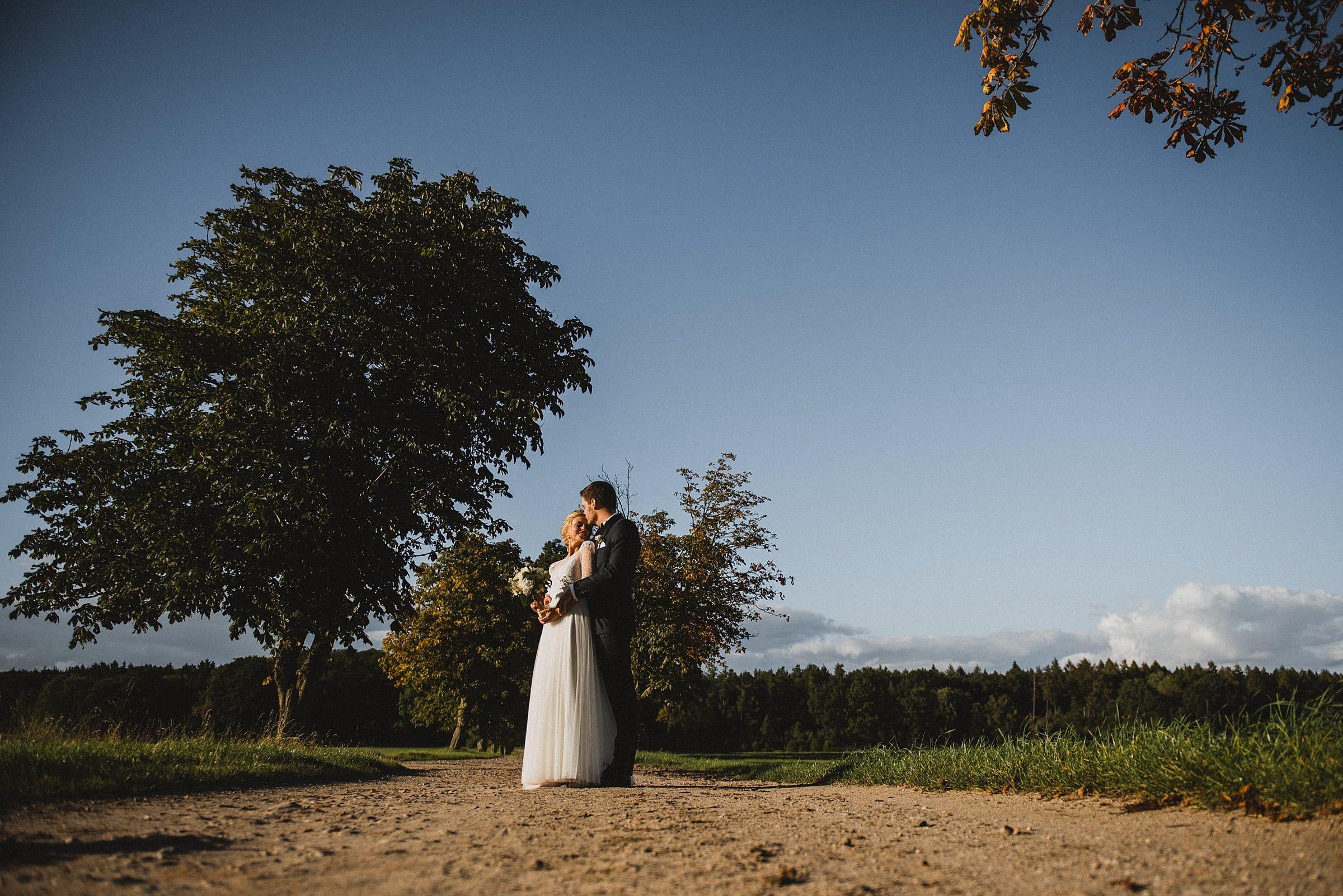 Hochzeitsfotografie Hamburg-Frau-Siemers-Gut Basthorst- Portrait Brautpaar- Ganzaufnahme- Brautpaar sonnt sich und genießt einen Moment der Ruhe