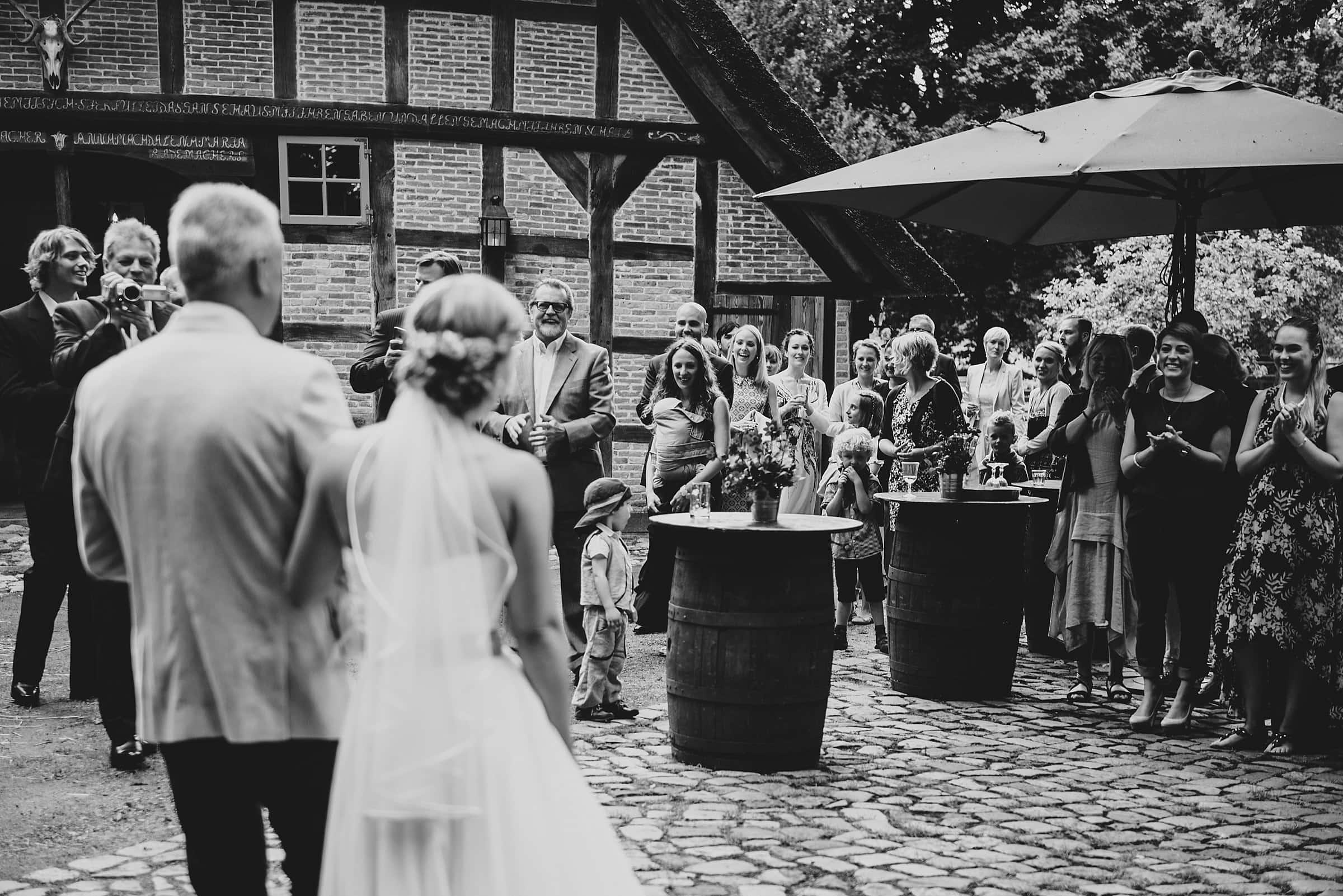 Hochzeitsfotografie-Frau-Siemers-Hof Weihe-Braut trifft am Hof ein und wird von den Gästen empfangen