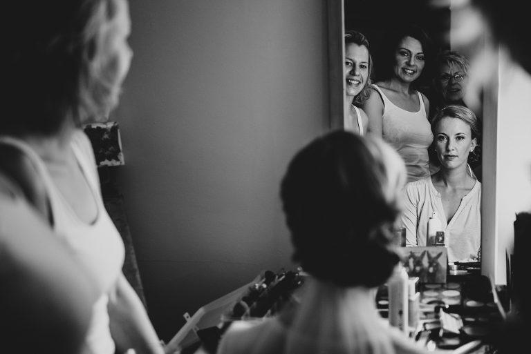 Hochzeitsfotografie-Frau-Siemers-Hof Weihe-Getting Ready- Trauzeuginnen und Brautmutter betrachten die. Braut im Spiegel und sind ganz gerührt