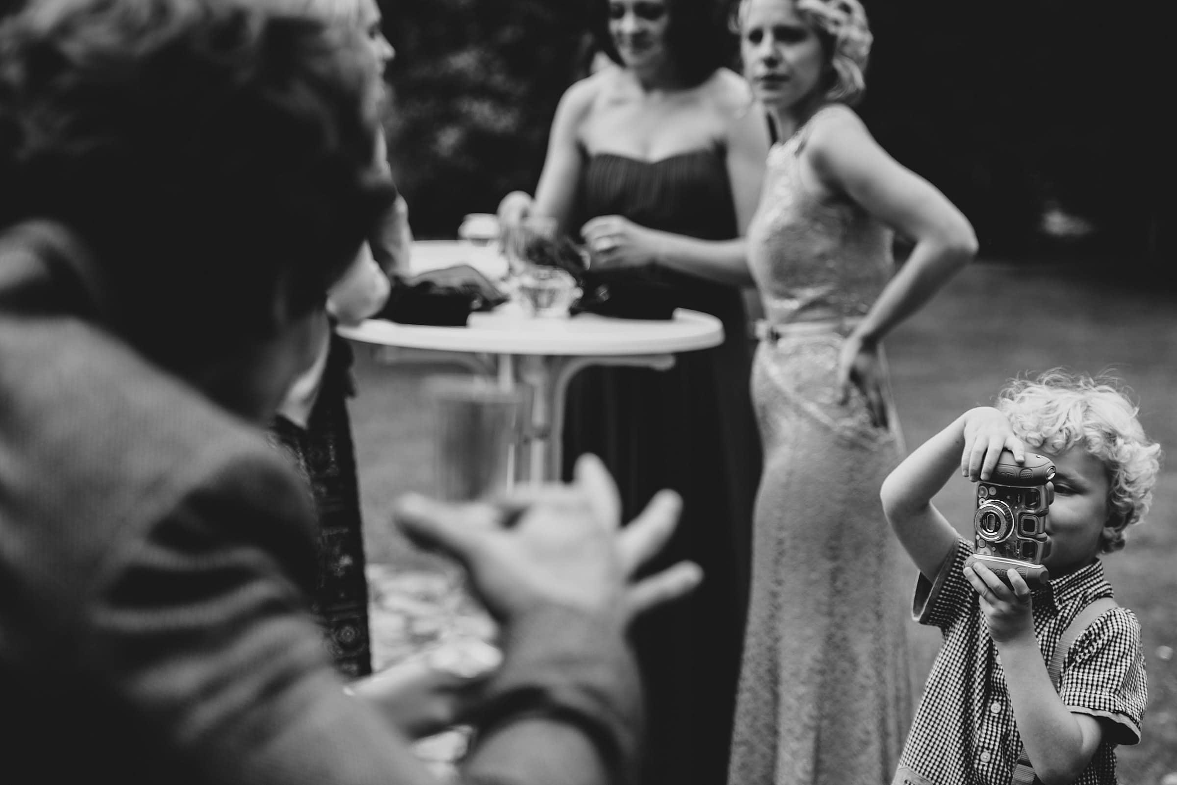 Hochzeitsfotografie-Frau-Siemers-Hof Weihe-Kleiner Junge macht ein Bild vom Bräutigam