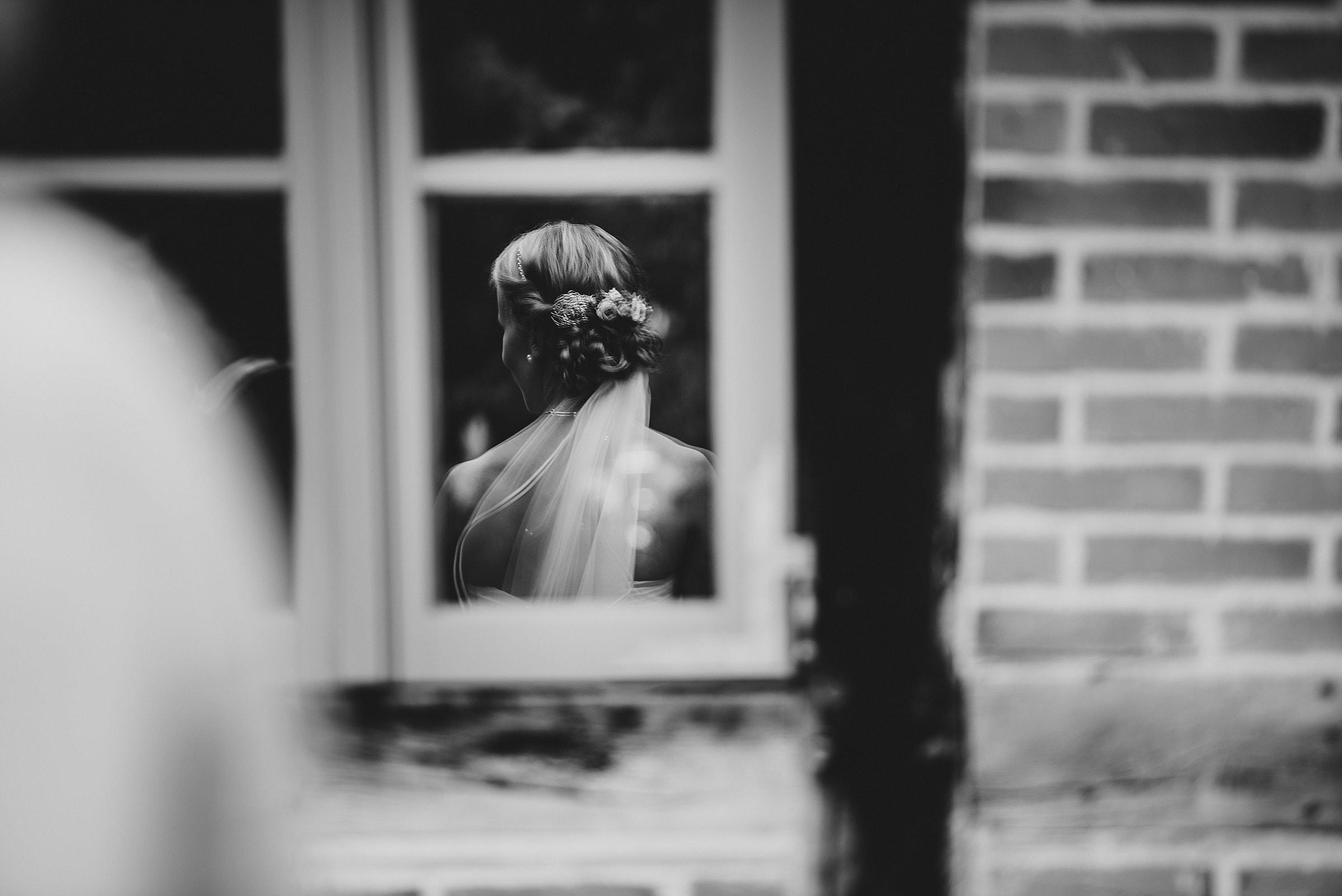 Hochzeitsfotografie-Frau-Siemers-Hof Weihe-Spiegelung der Braut im Fenster