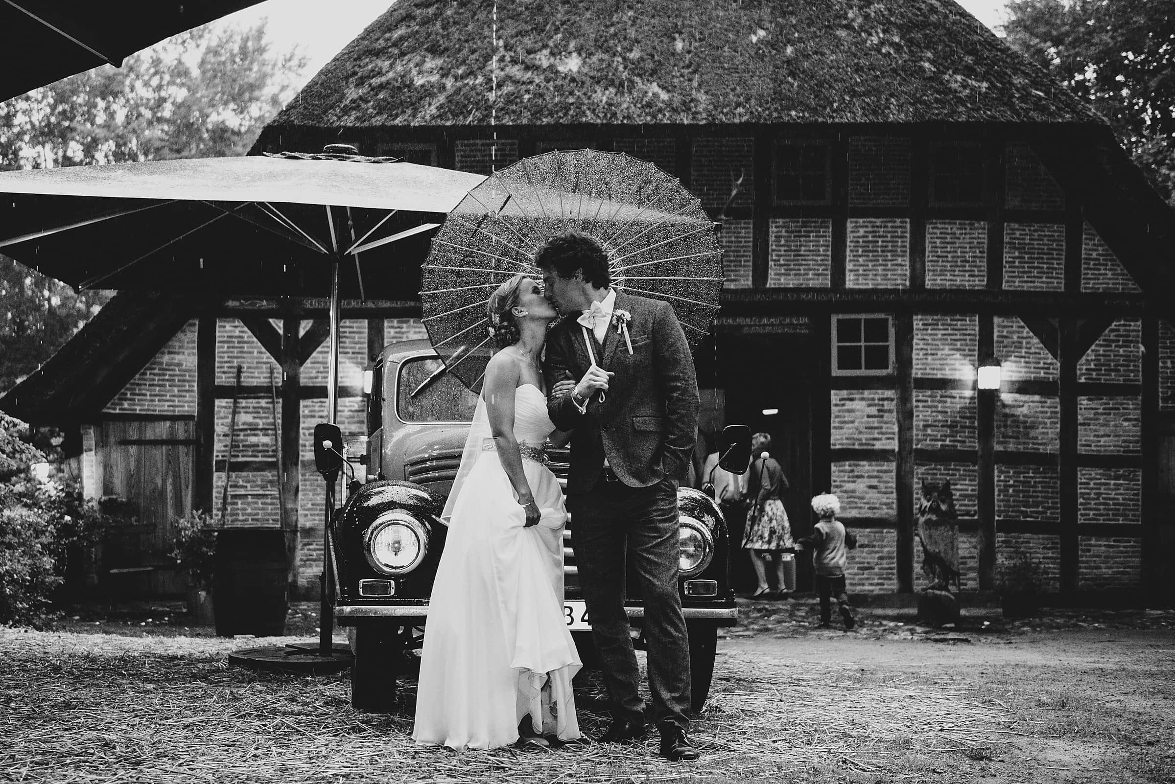 Hochzeitsfotografie-Frau-Siemers-Hof Weihe-Brautpaar steht im Regen und küsst sich