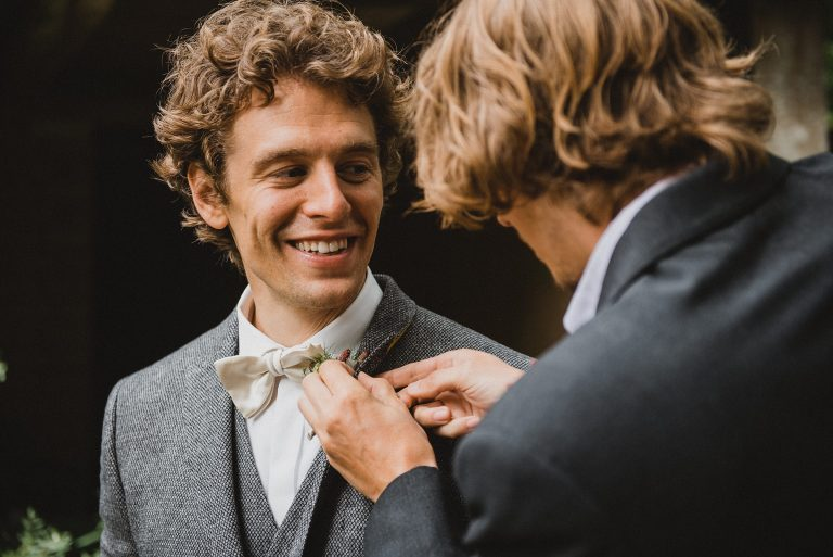 Hochzeitsfotografie-Frau-Siemers-Hof Weihe-Nahaufnahme Bräutigam der sich über das anstecken seiner Blume freut.