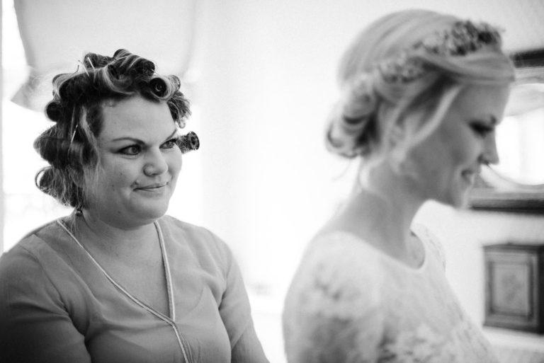 Brautschwester noch mit Haarwicklern im Haar, hilft der Braut beim anziehen des Kleides.