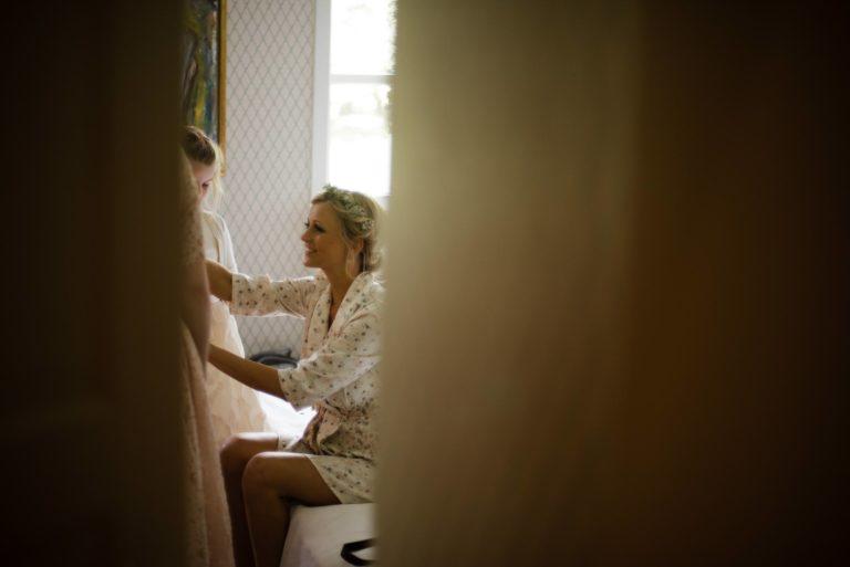 Beginn des Getting Readys- Braut sitzt auf dem Bett spricht mit dem Blumenkind