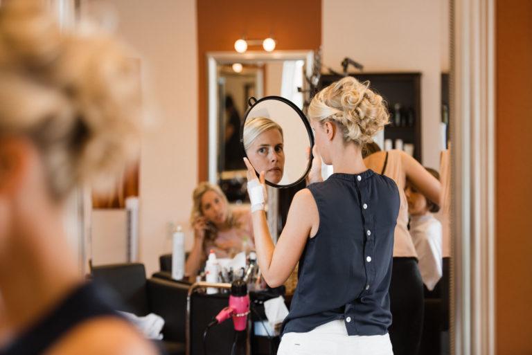 Hochzeitsfotografie Sankt-Peter Ording- Getting Ready Strandgut Resort- Braut schaut sich im Spiegel an.