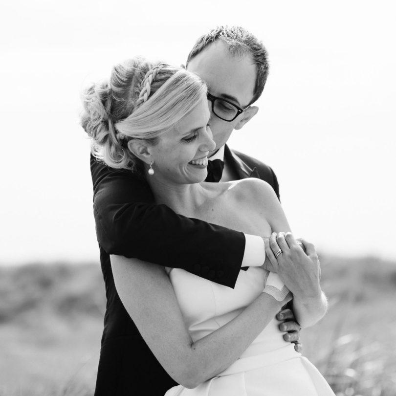 Hochzeitsfotografie Sankt-Peter Ording- Hochzeitsbilder am Strand- Bräutigam umarmt Braut von hinten und küsst sie auf die Wange.