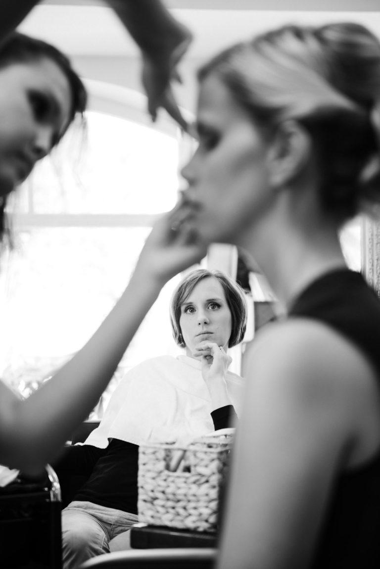 Hochzeitsfotografie Sankt-Peter Ording- Getting Ready Strandgut Resort- Male up anlegen der Braut, Trauzeugin schaut interessiert zu.