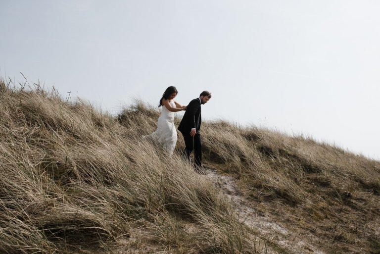 Sankt-Peter-Ording- Hochzeitsbilder- Mit Blick auf die Dünen. Brautpaar auf dem Weg zum Meer.