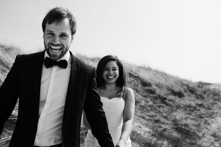Sankt-Peter-Ording- Hochzeitsbilder- Mit Blick auf die Dünen. Brautpaar lacht in die Kamera