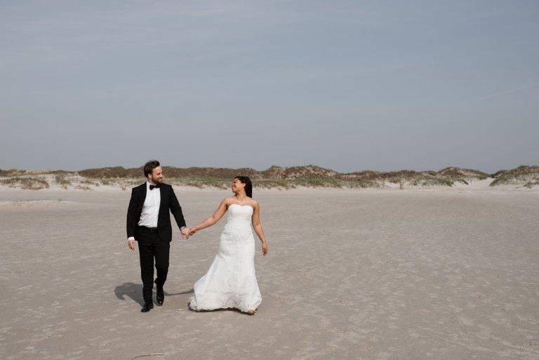 Sankt-Peter-Ording- Hochzeitsbilder- Hochzeitspaar geht Hand in Hand den Strand entlang.