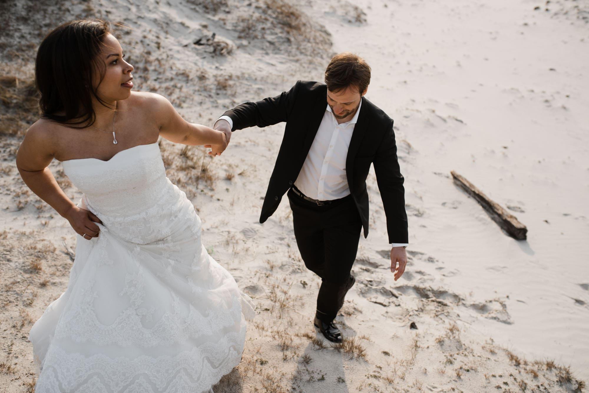 Sankt-Peter-Ording- Hochzeitsbilder- Brautpaar geht Hand in Hand den Dünenweg entlang.