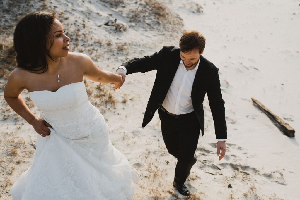 Frau-Siemers. Hochzeitsfotografie Hamburg. Brautpaar, dass eine Düne in Sankt-Peter Ording hinauf läuft.