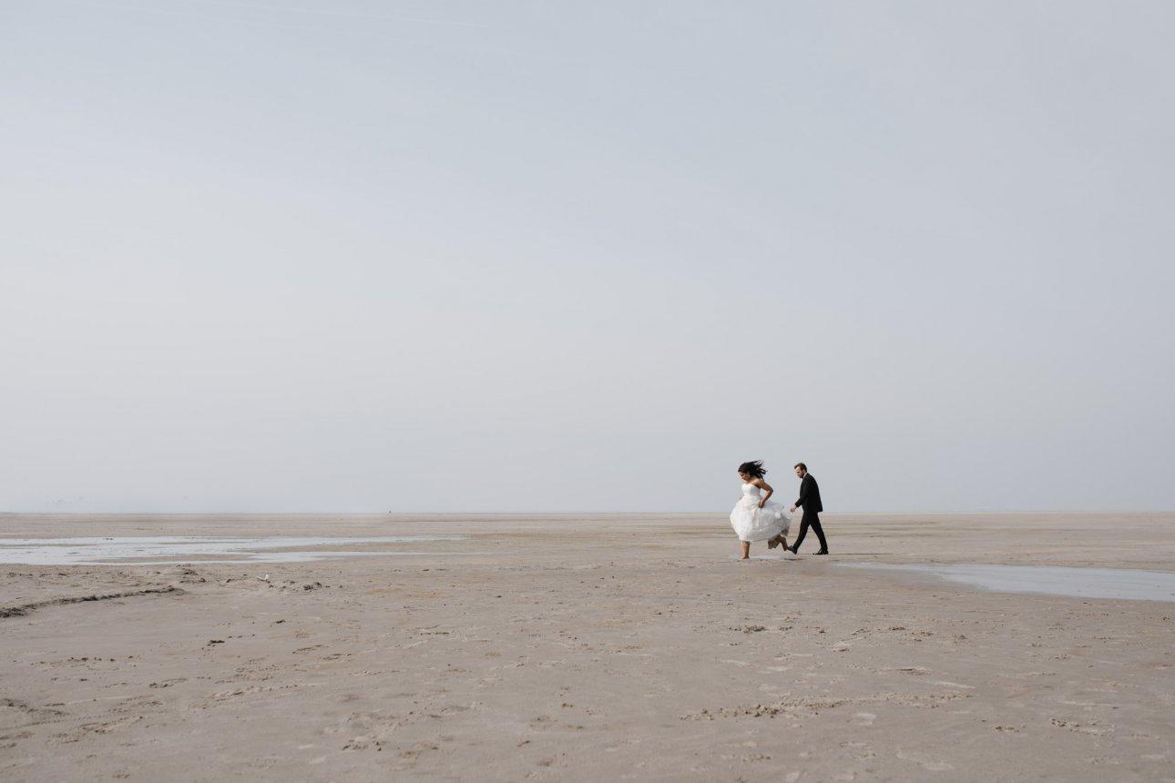 Sankt-Peter-Ording- Hochzeitsbilder- Weiter Strand mit Brautpaar.