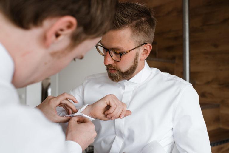 Hochzeitsfotografie Bremen- Getting Ready Bräutigam. Trauzeuge Hilfe dem Bräutigam mit den Manschettenknöpfen.