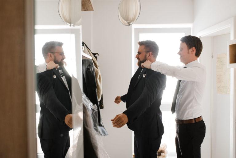 Hochzeitsfotografie Bremen- Getting Ready Bräutigam. Trauzeuge hilft Bräutigam ins Sakko.