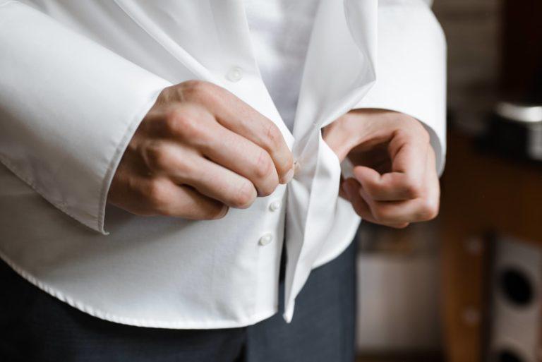 Hochzeitsfotografie Bremen- Hochzeitsdokumentation- Getting Ready- Detail zuknöpfen des Hemdes.