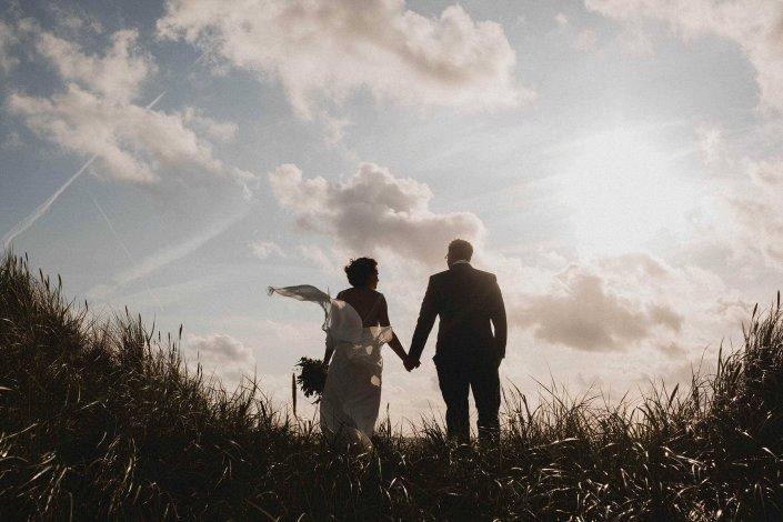 Hochzeitsfotografie Sankt-Peter-Ording. Brautpaar steht in den Dünen und schaut aufs Meer. Der Wind lässt das Brautkleid wehen.