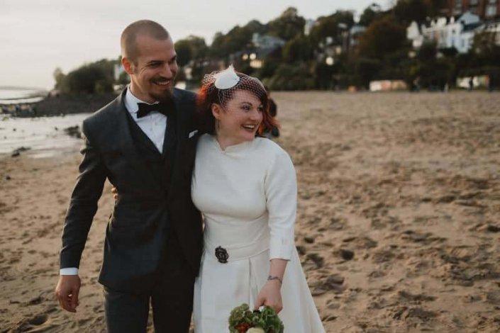 Hochzeitsfotografie-Frau-Siemers-Hochzeitsbild am Elbstrand-Brautpaar geht den Elbstrand entlang und schaut in die Weite