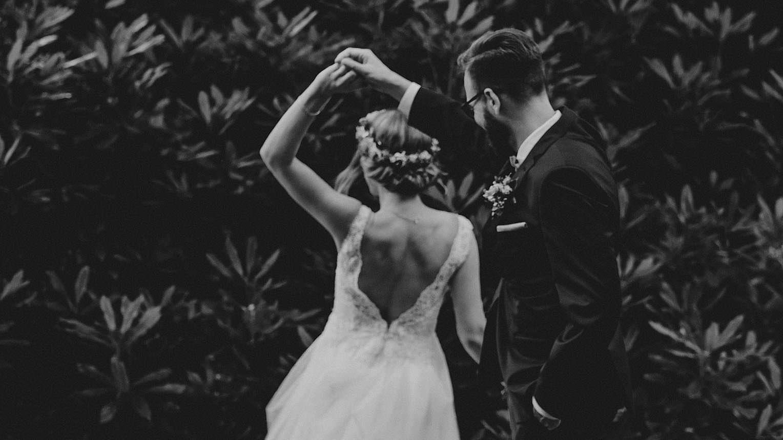 Hochzeitsfotografie-Frau-Siemers- Brautpaar Tanzt vor Busch - schwarz/weiß Portrait