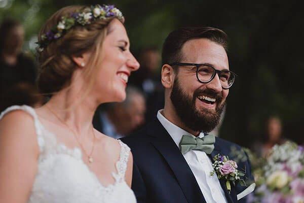 Hochzeitsfotografie-Frau-Siemers-standesamtliche Trauung am Weiher in Hamburg- Brautpaar lacht während der Trauung.