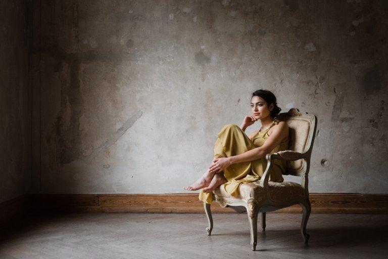 Brautmode Hamburg- AveevA- Model sitzt auf einem Stuhl und blickt aus dem Fenster