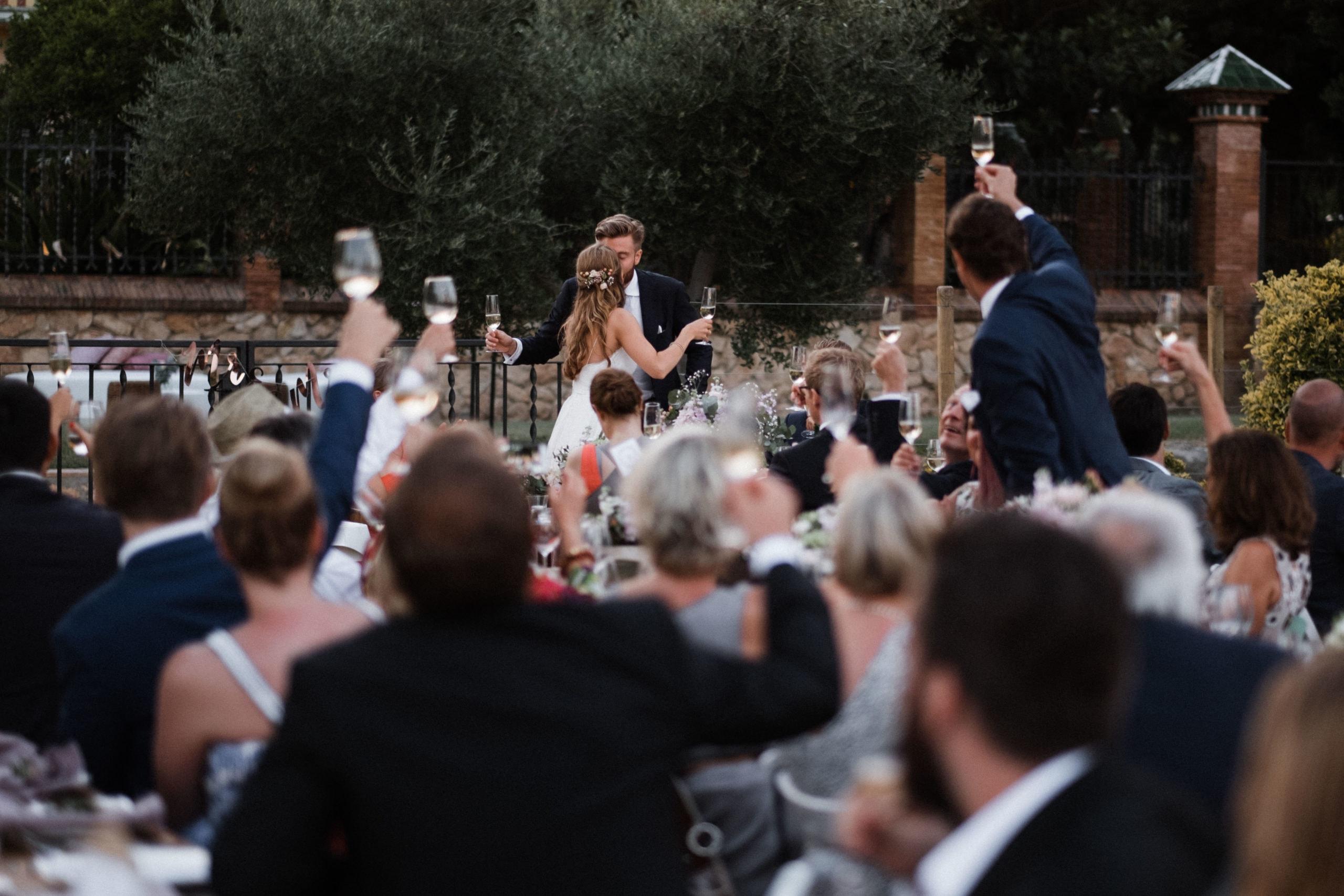 das Brautpaar küsst sich vor seinen Gästen, sie stehen in dem Garten eines Weingut in Barcelona, die Gäste heben ihre Gläser in die Luft