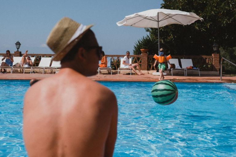 ein Mann sitzt auf dem Rand eines Pool, der zu einem Weingut in Barcelona gehört, der Mann schaut zur Sete, ihm gegenüber steht ein kleiner Jnge am Beckenrand, vor ihm fällt ein Wasserball, der aussieht, wie eine Wassermelone, in den Pool, die Sonne reflektiert in dem Wasser