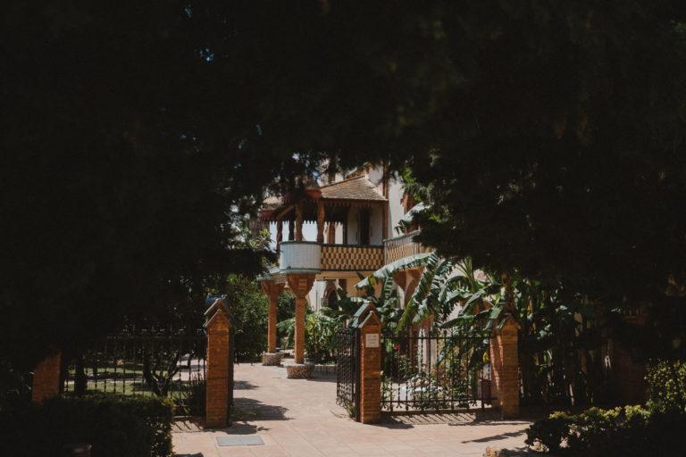 das Tor zu dem Eingang des Weingutes in Barcelona, es ist umringt von Palmen, die Sonne scheint, 2 Holzsäulen sind am Eingang des Gut