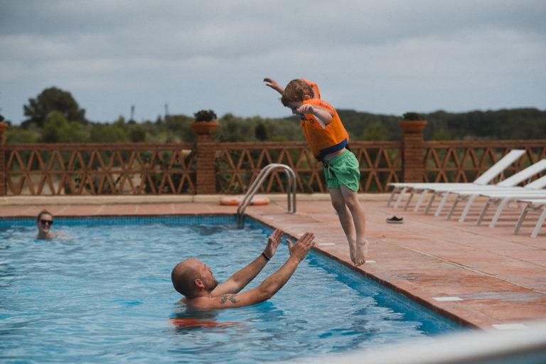 der Pool eines Weingut in Barcelona, ein kleiner Junge springt mit den Kopf voran in den Pool, vor ihm in dem Pool ist ein Mann, der ihm die Arme entgegenstreckt