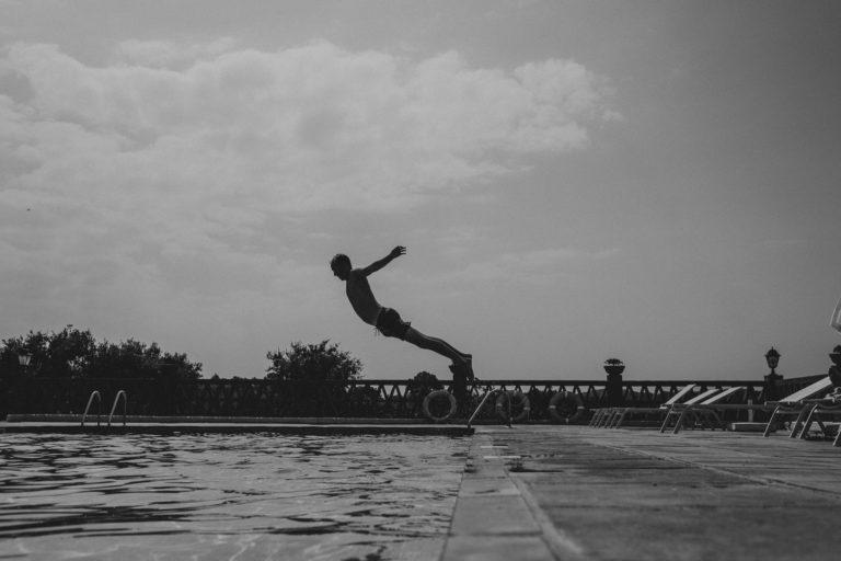 ein Pool eines Weingut in Barcelona, ein Mann springt von einem Startblock gestreckt in den Pool