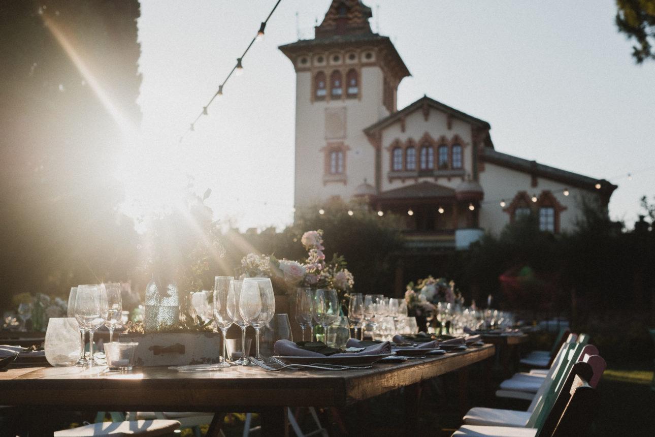 ein gedeckter Tisch in dem Garten eines Weingut in Barcelona, die Sonne geht langsam unter, im Hintergrund stht das Weingut
