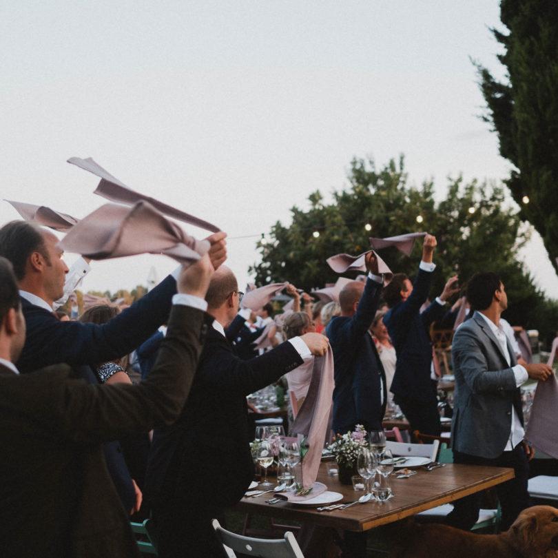 die Gäste des Brautpaarstehen an großen Tischen in dem Garten eines Weingut in Barcelona, über ihnen hängen Glühbirnenlichterketten, die Sonne geht langsam unter, die Gäste schwingen über ihren Köpfen große Leinentücher