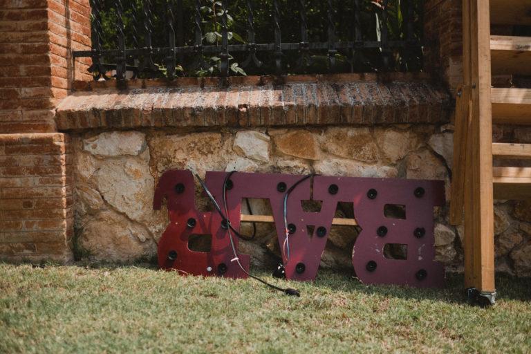 ein einem Garten eines Weingut in Barcelona liegt angelehnt an einer Steinmauer ein Schild, es steht auf dem Kopf, Kabel sind um das Schild gewickelt, das Schild hat die Umrisse des Wortes