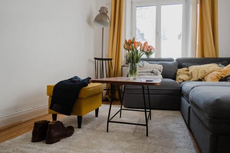ein Wohnzimmer mit großen Sofa, es steht ein Tulpenstrauß auf dem kleinen Tisch, auf dem gelben Hocker liegt ein Sakko, davor stehen braune Schuhe