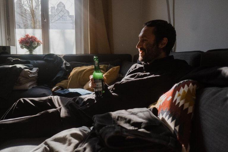 ein Mann sitzt auf dem Sofa, er hält ine Flasche Bier in der Hand, die Sonne scheint durch das Fenster