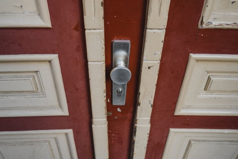 eine rote Eingangstür mit weißen Details, im Fokus ist der silberne Türknauf