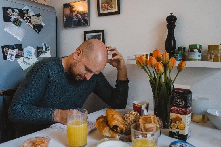 der Bräutigam sitzt in der Küche, der Frühstückstisch ist gedeckt , er stützt sich an seinem Arm ab