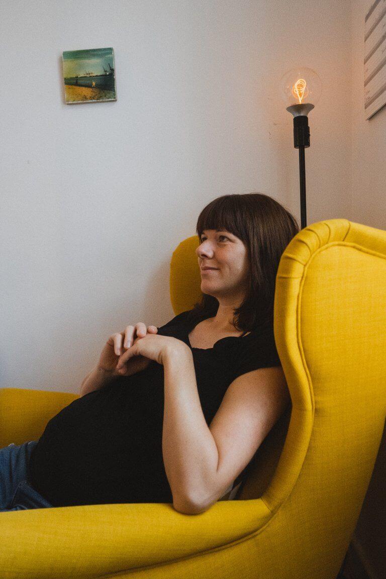 die Braut sitzt in einem gelben Sessel, ihre Hände liegen auf ihrem Bauch (sie ist schwanger)