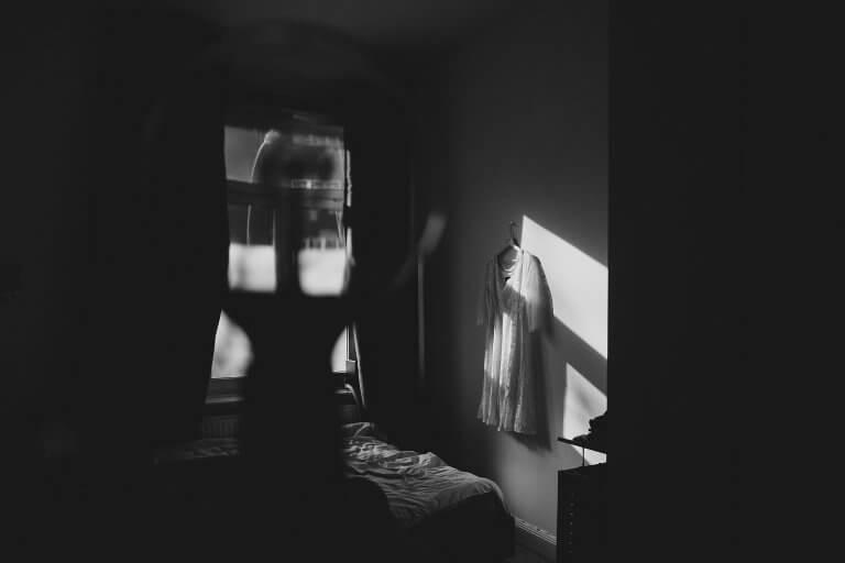in einem Raum hängt das Brautkleid an der Wand, die Sonne scheint durch das Fenster, es entsteht ein Licht- und Schattenspiel, im Vordergrund ist eine Glühbirne