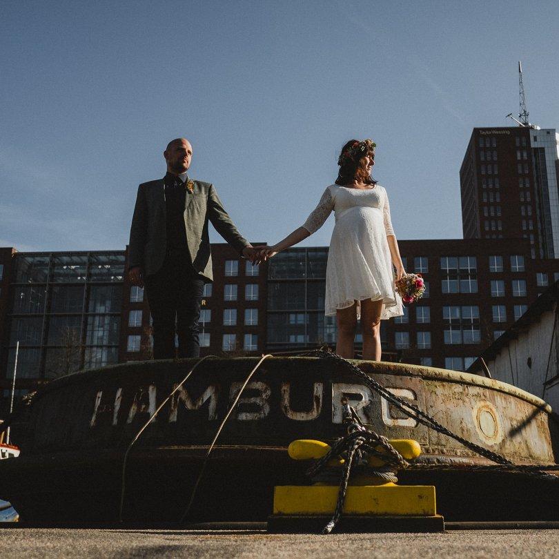 das Brautpaar steht in Hamburg auf einem großen Schiff, sie halten ihre Hand, hinter ihnen ist ein großes Gebäude