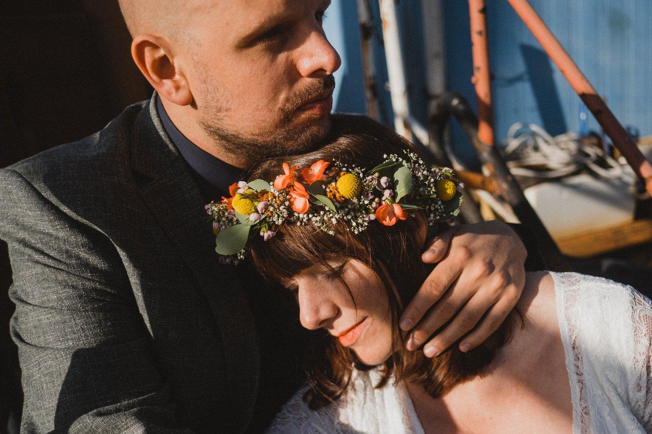 der Bräutigam hält die Braut an seinen Oberkörper, sie schließt ihre Augen, er schaut in die Ferne, sie sitzen draußen am Hafen in Hamburg