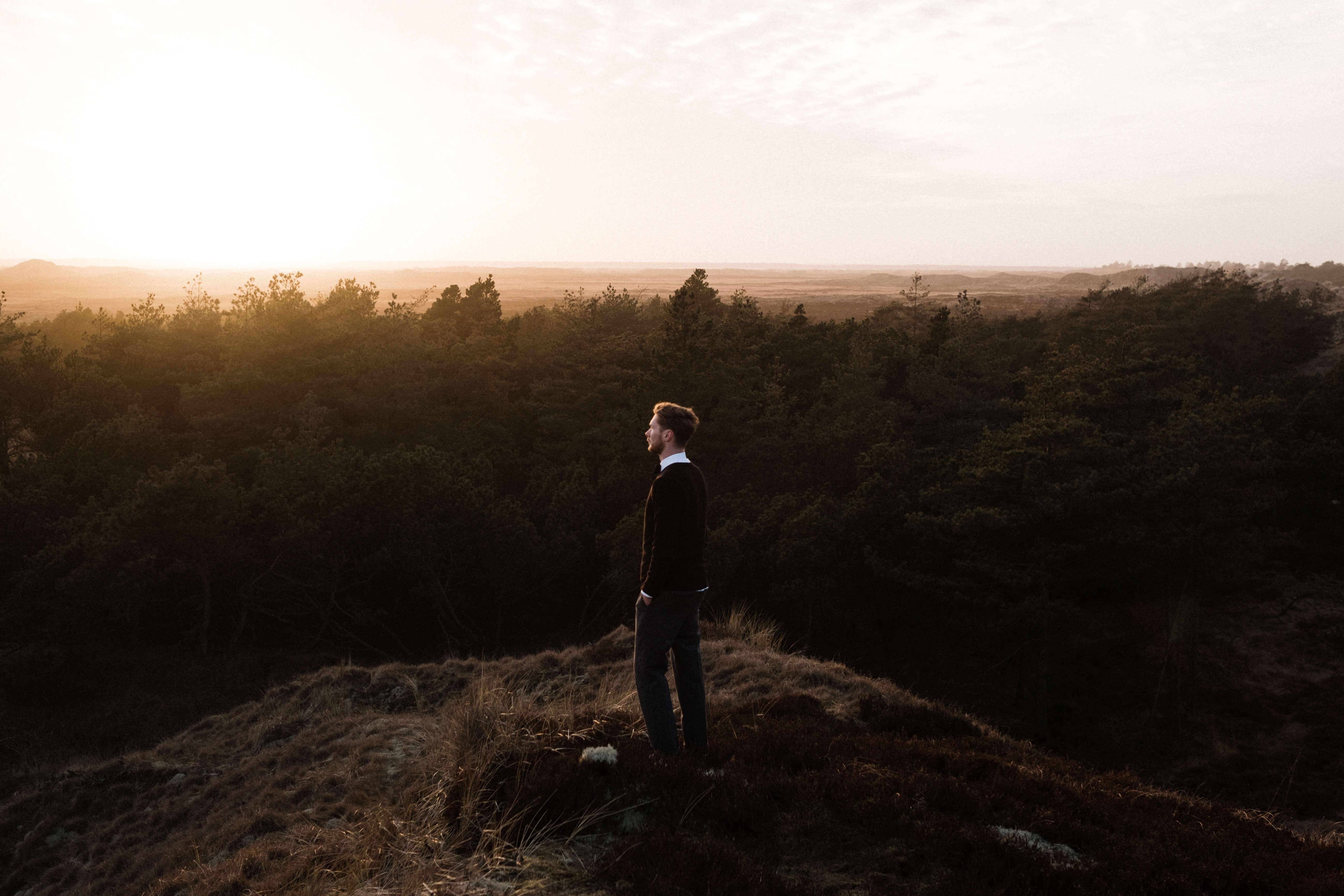 Zu sehen ist ein Mann, der auf einem Berg steht. Die Sonne geht fast unter.