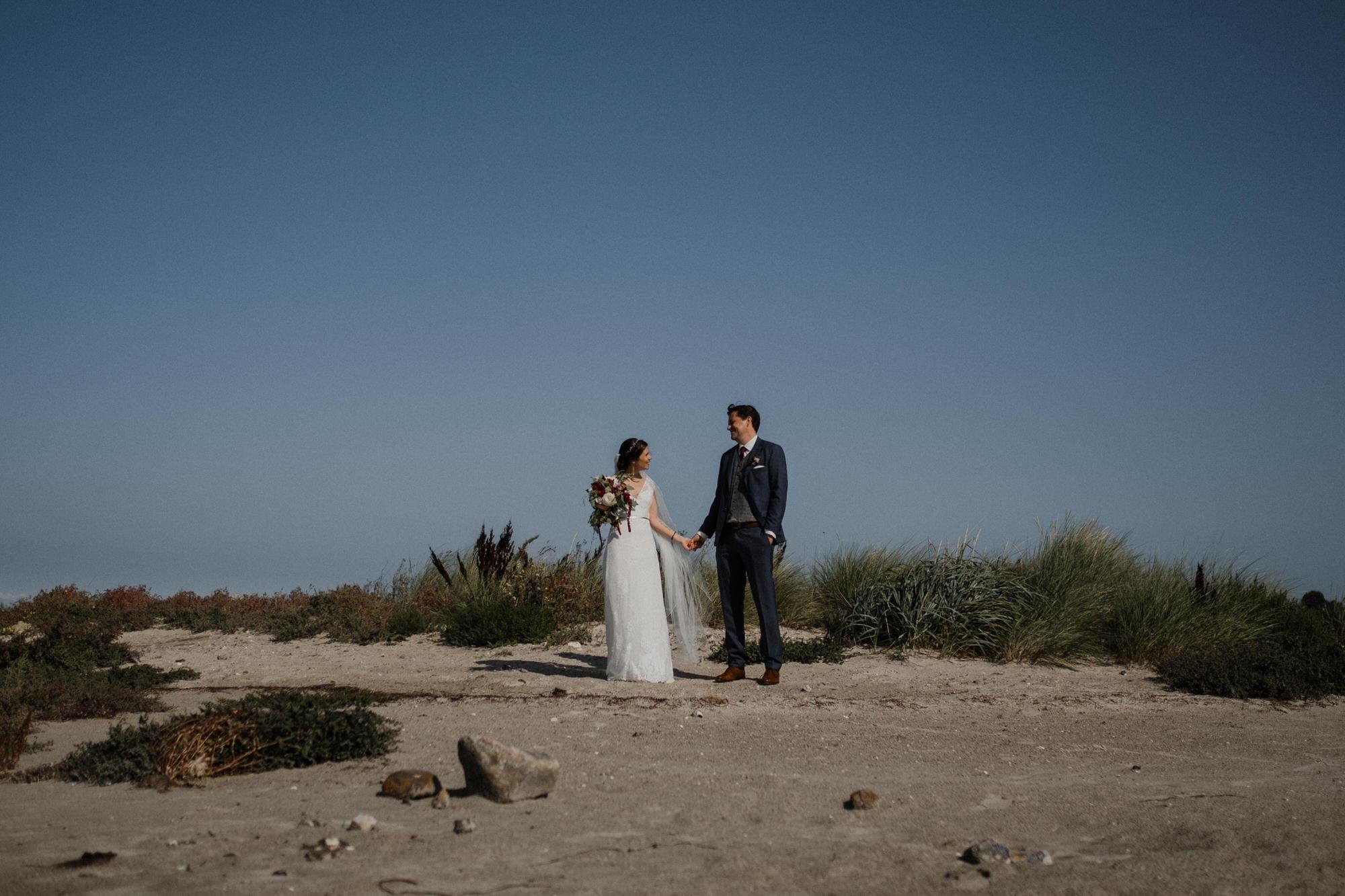 Hochzeitsfotografie Kiel- Hochzeitsbilder am Meer. Brautpaar Hand in Hand am Strand.
