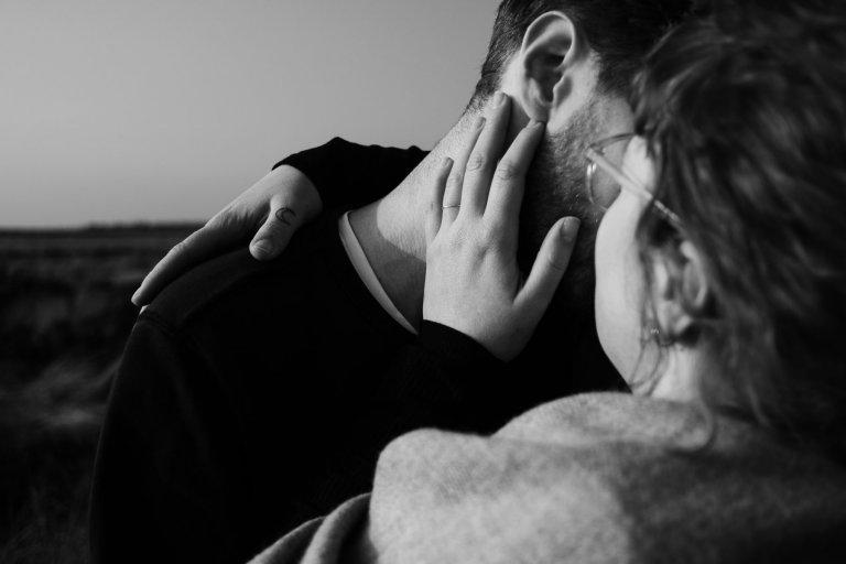 ein Paar küsst sich, ihre Hand berührt seinen Hals