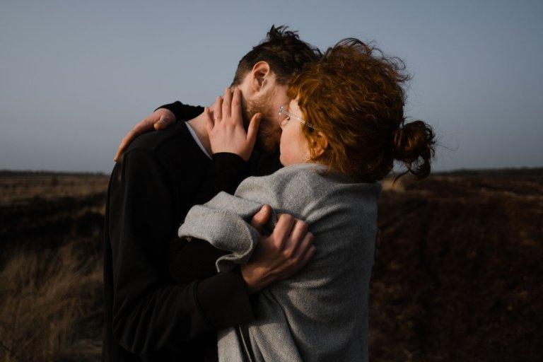 das Paar hält sich einander fest, sie küsst seine Wange, im Hintergrund ist das Uchter Moor zu sehen