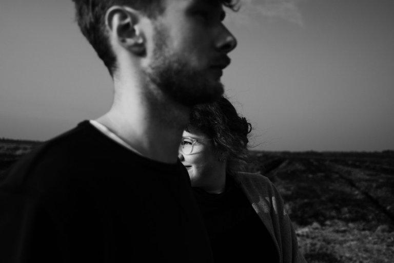 im Vordergrund steht ein Mann, hinter ihm steht eine Frau, sie schauen in unterschiedliche Richtungen